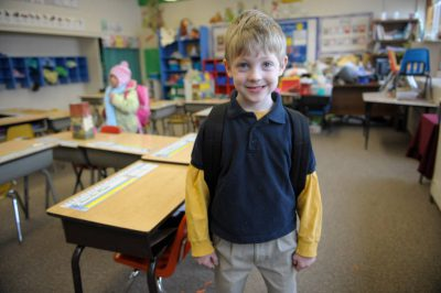 Photo: A boy stands in his kindergarten classroom.