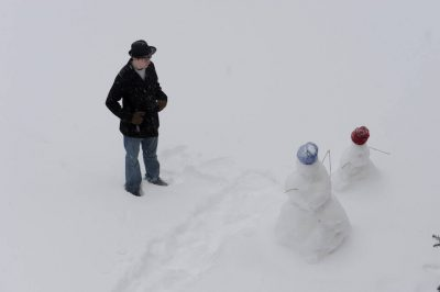 Photo: A teenage boy stands with snowmen.