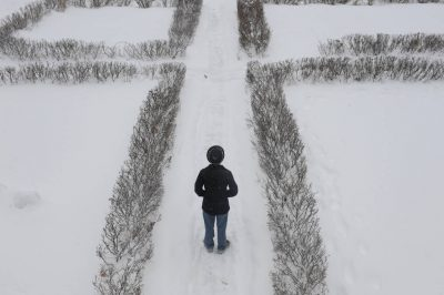 Photo: A teen boy stands on the snowy sidewalk in front of his house.