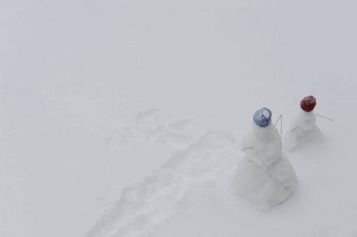 Photo: Two snowmen stand together.