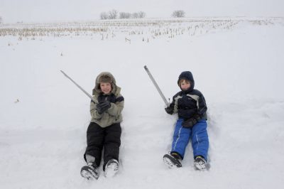 Photo: Two boys sit in the snow on a farm in Nebraska.