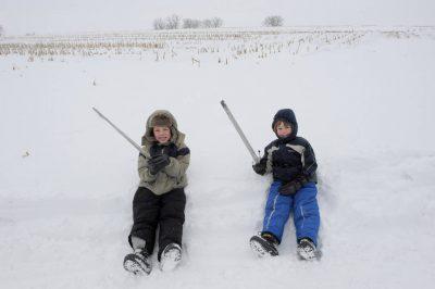 Photo: Two boys sit in the snow on a farm in Nebraska.