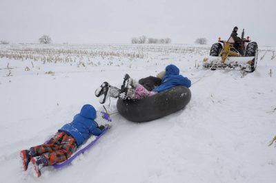 Photo: Three children ride sleds behind a tractor on a farm in Nebraska.