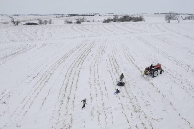 Photo: After falling off an innertube, a boy runs to catch up to a tractor sleigh ride on a farm near Cortland, NE.