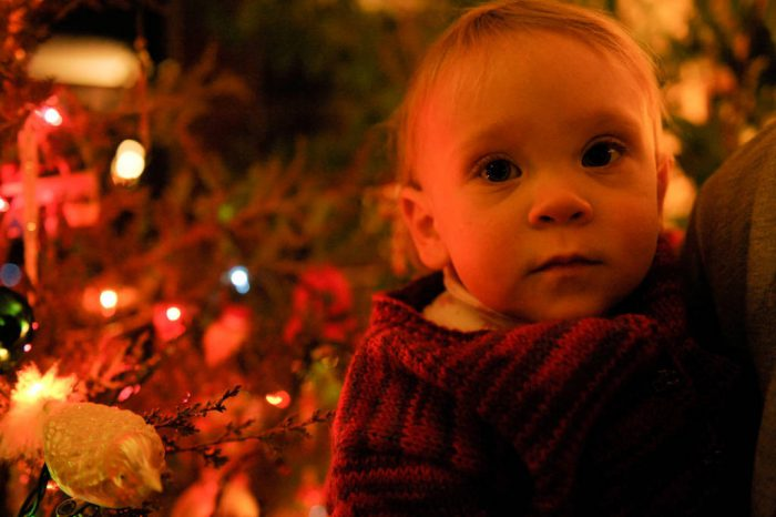 Photo: A infant in front of a Christmas tree.