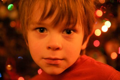 Photo: A young boy in front of a christmas tree.