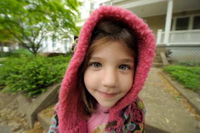 Photo: Portrait of a young girl wearing a pink hood.