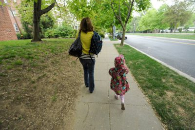 Photo: A mother and daughter walk down the street.
