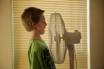 Photo: A seven year-old boy talks into a fan.