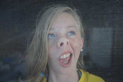 Photo: A young girl distorting her face against a screen door in Leech Lake, Minnesota.