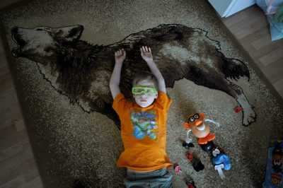Photo: A young boy plays with his toys on a wolf rug at a cabin in Leech Lake, Minnesota.