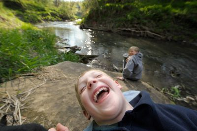 Photo: A young boy laughs while sitting along a stream with his sister near Dunbar, Nebraska.