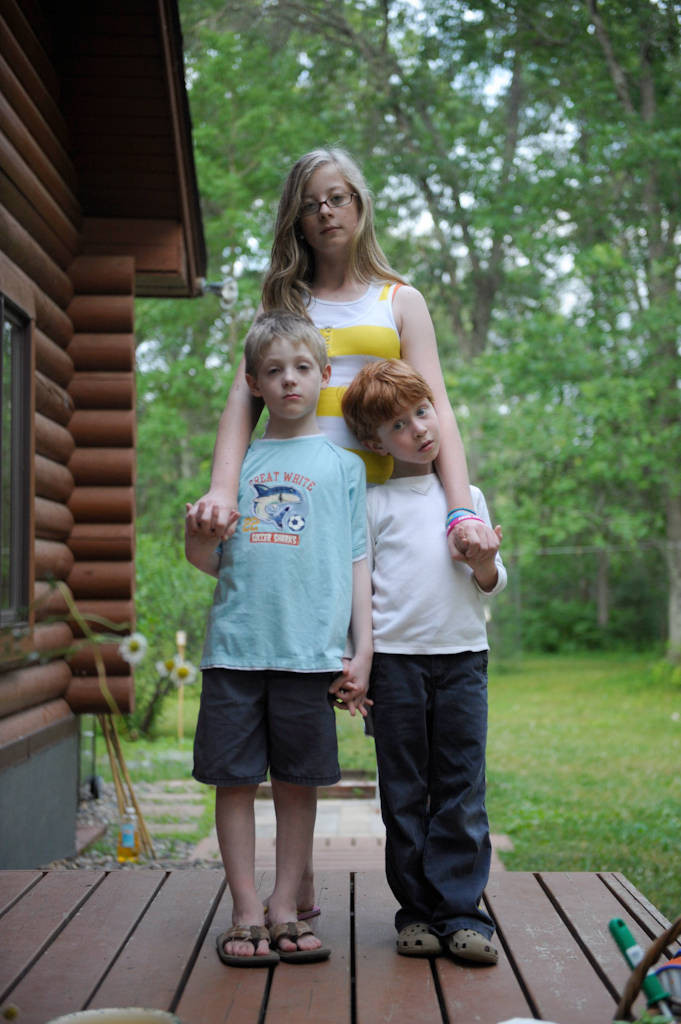 Photo: A young woman holding hands with her brother and cousin at their home in Crosslake, Minnesota.
