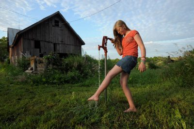 Photo: A young woman rinses her feet off at a water pump at her farmhouse in Dunbar, Nebraska.