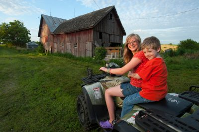 Photo: A sister and brother ride together on an ATV at their farmhouse in Dunbar, Nebraska.