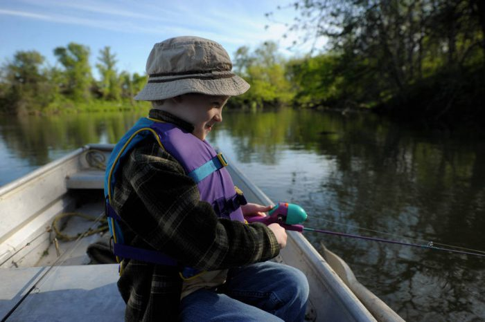Photo: A young boy fishing from a boat on a pond near Ceresco, Nebraska.
