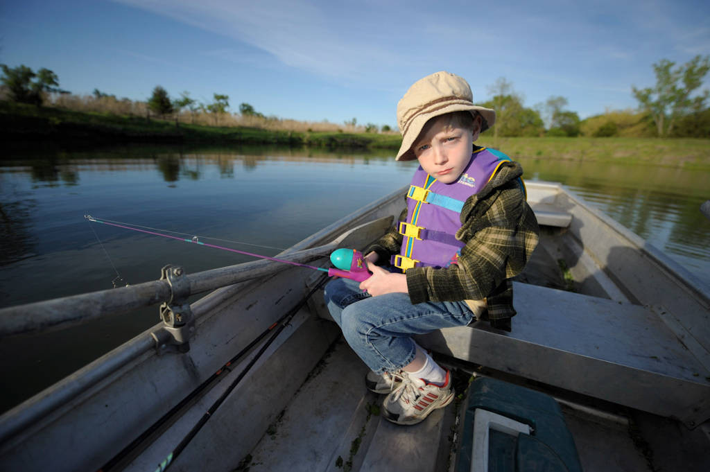 Photo: A young boy fishing in a boat on a pond near Ceresco, Nebraska.