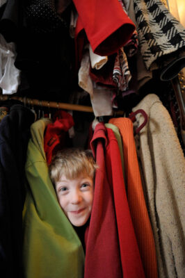 Photo: A six year-old boy plays in a closet full of clothes.