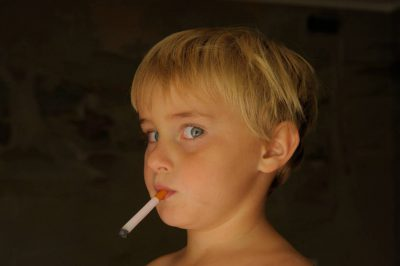 Photo: A young boy pretending to smoke gum cigarrettes at his home in Lincoln, NE.