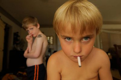 Photo: Two young boys pretend to smoke gum cigarrettes.