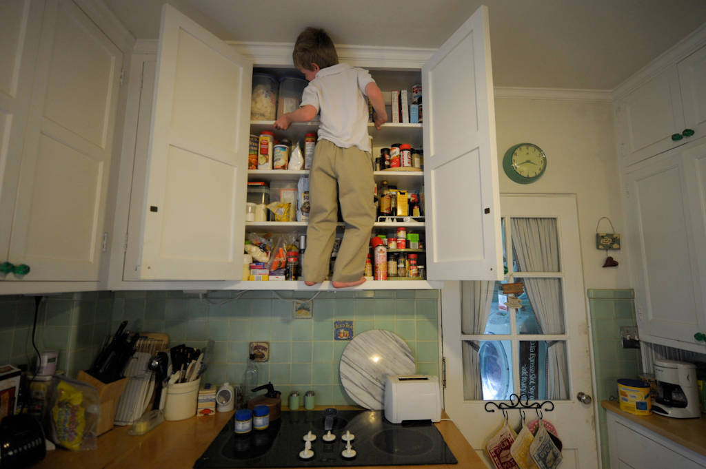 Photo: A young boy climbs and forages for food in his kitchen at his home in Lincoln, Nebraska.