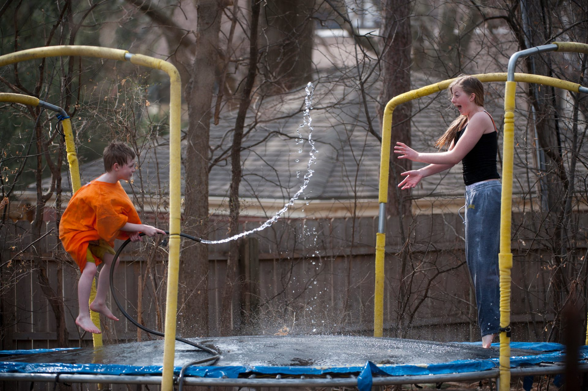 Photo: A brother and sister have a water fight on their trampoline.