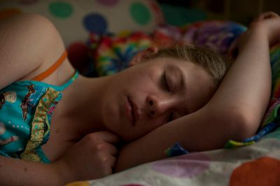 Photo: A teenage girl comfortably sleeps in her room.