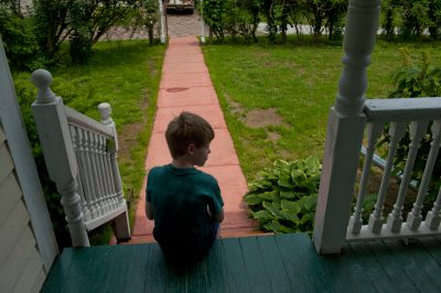 Photo: A young boy sits on a porch.