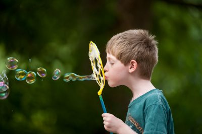 Photo: A young boy blows bubbles.