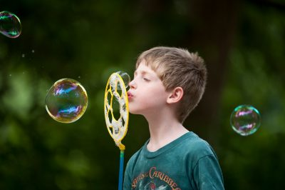 Photo: A young boy blows bubbles.