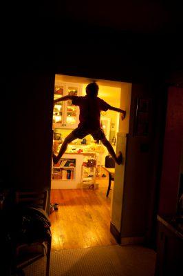 Photo: A young boy climbs a door frame.
