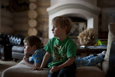 Photo: Two boys watch TV while on vacation.