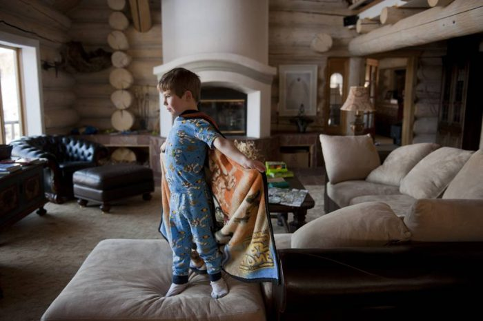 Photo: A young boy plays inside a cabin.