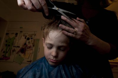 Photo: A young boy suffers through a haircut.