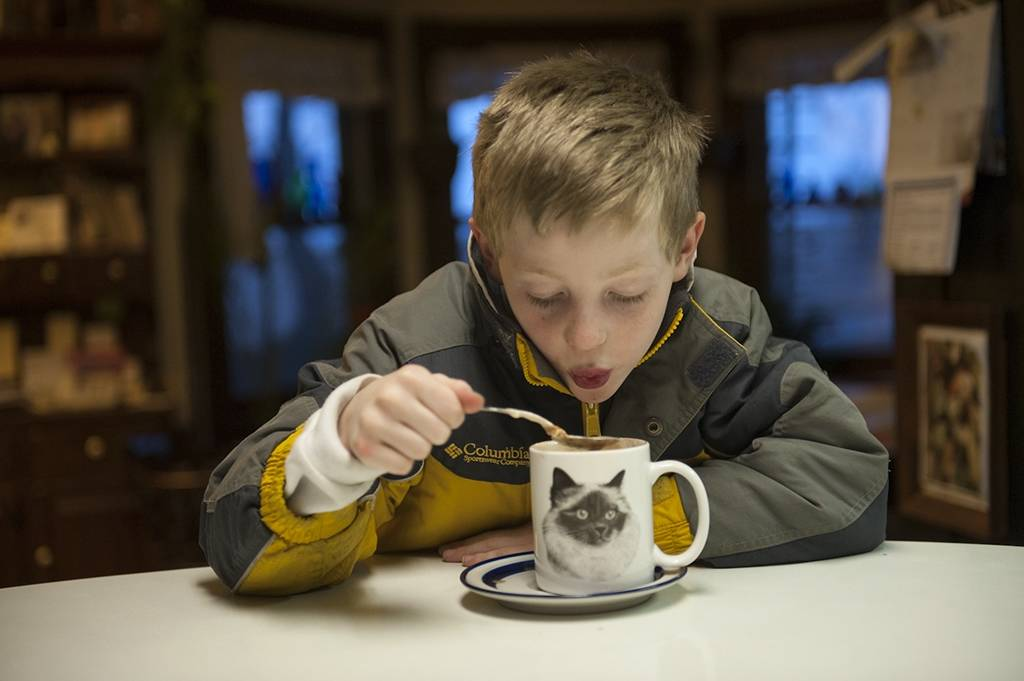 Photo: A young boy drinks hot cocoa.