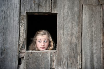 Photo: A teenage girl looks out of a barn window.