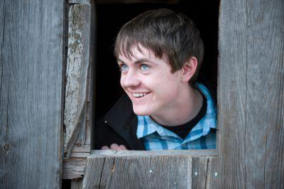 Photo: A teenage boy looks out of a barn window.