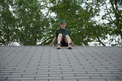Photo: A young boy perched on the top of a roof.