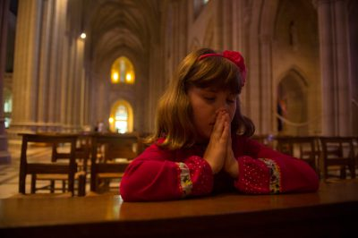 Photo: A young girl prays in the National Cathedral, Washington, District of Columbia.