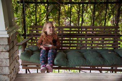 Photo: A little girl sits on a porch swing in Lincoln, Nebraska.