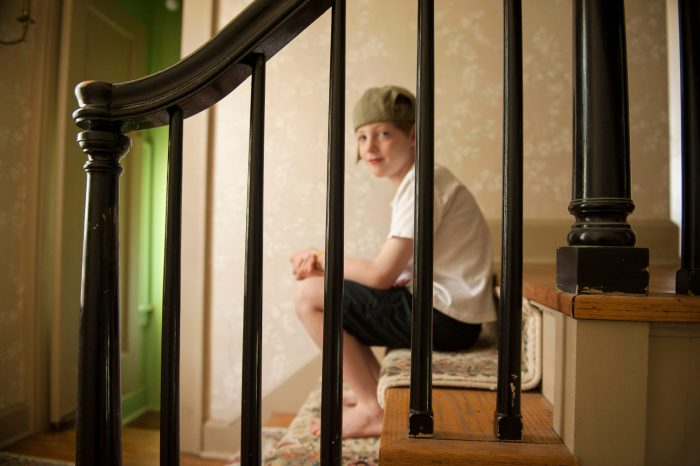 Photo: A boy sits on the stairs at his home in Lincoln, Nebraska.