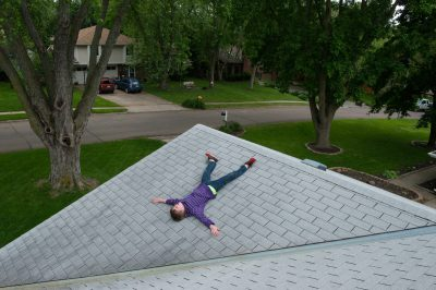 Photo: An elementary age boy laying on the roof of his grandparent's house.
