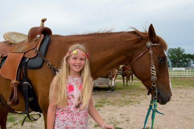 Photo: An elementary age girl stands next to her horse.