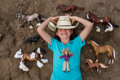 Photo: An elementary age girl lays on the ground surrounded by her toy horses.