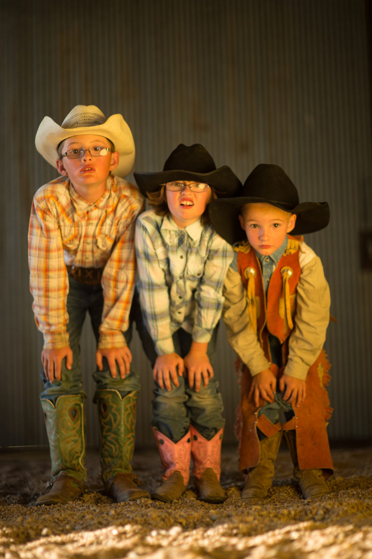 Photo: Portrait of three elementary age siblings wearing cowboy hats and boots.