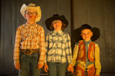 Photo: Portrait of three elementary age siblings wearing cowboy hats.