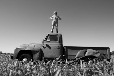 Photo: A young woman stands on top of an old International Harvester truck on a farm in Bennet, Nebraska.