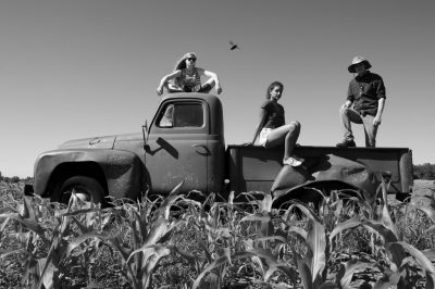 Photo: Three teenagers pose on top of an old International Harvester truck on a farm in Bennet, Nebraska.