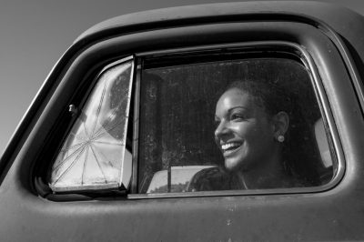 Photo: A young woman looks out from an old International Harvester truck in Bennet, Nebraska.
