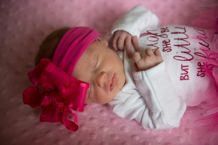 Photo: A newborn baby girl with a pink bow on her head.